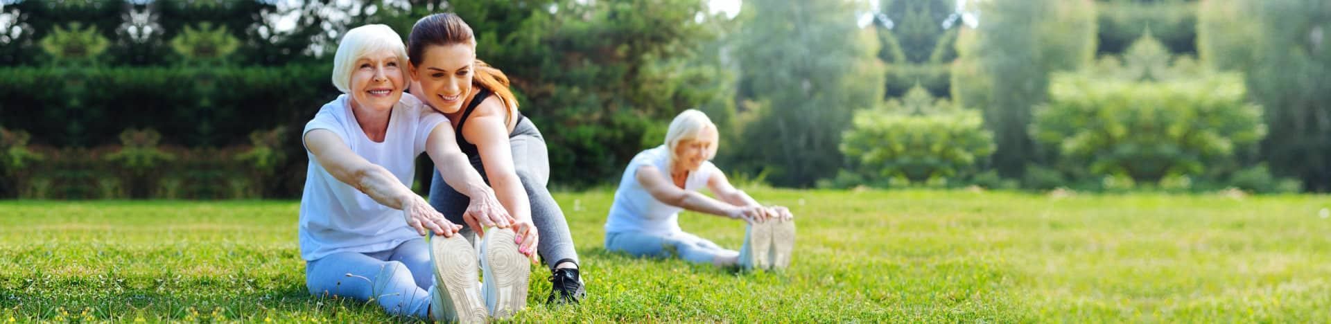 woman helping old woman to excercise