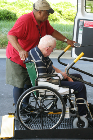 man helps old man into a wheelchair equipped van